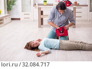 Купить «Young couple in first aid concept at home», фото № 32084717, снято 10 мая 2019 г. (c) Elnur / Фотобанк Лори
