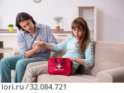 Купить «Young couple in first aid concept at home», фото № 32084721, снято 10 мая 2019 г. (c) Elnur / Фотобанк Лори