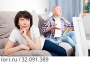Купить «Sad woman sitting on the sofa. Next to her husband watching TV», фото № 32091389, снято 27 мая 2019 г. (c) Яков Филимонов / Фотобанк Лори