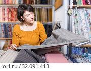 Купить «Woman looking for cloth in shop», фото № 32091413, снято 7 февраля 2019 г. (c) Яков Филимонов / Фотобанк Лори