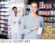 Купить «Smiling female client is satisfied of recommended medicine in apothecary.», фото № 32091441, снято 28 февраля 2018 г. (c) Яков Филимонов / Фотобанк Лори