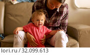 Mother with baby sitting on sofa. Стоковое видео, видеограф Ekaterina Demidova / Фотобанк Лори