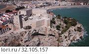 Купить «Picturesque aerial view of coastal line of Spanish tourist town of Peniscola with medieval castle on crag», видеоролик № 32105157, снято 16 апреля 2019 г. (c) Яков Филимонов / Фотобанк Лори