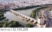 Купить «Aerial view of cityscape of Cordoba with Roman Bridge over the Guadalquivir and the Mosque-Cathedral of Cordoba», видеоролик № 32105209, снято 22 апреля 2019 г. (c) Яков Филимонов / Фотобанк Лори