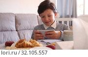 Купить «Boy looking to smartphone screen on sofa in domestic interior», видеоролик № 32105557, снято 12 июня 2019 г. (c) Яков Филимонов / Фотобанк Лори