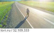 Купить «Flight over hitchhiker tourist walking on asphalt road. Huge rural valley at summer day. Backpack hiking guy.», видеоролик № 32109333, снято 1 августа 2018 г. (c) Александр Маркин / Фотобанк Лори