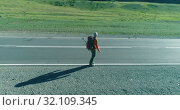 Купить «Flight over hitchhiker tourist walking on asphalt road. Huge rural valley at summer day. Backpack hiking guy.», видеоролик № 32109345, снято 3 августа 2018 г. (c) Александр Маркин / Фотобанк Лори