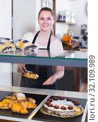 Купить «portrait of young positive woman baker with tasty cakes and rolls», фото № 32109989, снято 22 апреля 2017 г. (c) Яков Филимонов / Фотобанк Лори