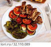 Grilled pork ribs rack garnished on white plate with eggplant; tomatoes and bell pepper. Стоковое фото, фотограф Яков Филимонов / Фотобанк Лори