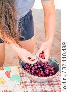 Купить «beautiful young woman washes cherries and eats», фото № 32110489, снято 7 июля 2019 г. (c) Акиньшин Владимир / Фотобанк Лори