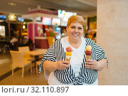 Купить «Fat woman holding ice cream in fastfood restaurant», фото № 32110897, снято 24 мая 2019 г. (c) Tryapitsyn Sergiy / Фотобанк Лори