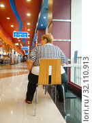 Fat woman sitting at the table, back view. Стоковое фото, фотограф Tryapitsyn Sergiy / Фотобанк Лори