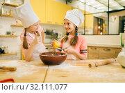 Купить «Little girls cooks in caps sniffing vanilla powder», фото № 32111077, снято 30 марта 2019 г. (c) Tryapitsyn Sergiy / Фотобанк Лори