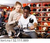 Купить «Happy young couple choosing and buying new motorcycle in moto salon», фото № 32111889, снято 16 января 2019 г. (c) Яков Филимонов / Фотобанк Лори