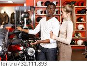 Купить «Happy young couple choosing and buying new motorcycle in moto salon», фото № 32111893, снято 16 января 2019 г. (c) Яков Филимонов / Фотобанк Лори