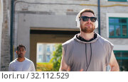 Купить «male friends with headphones running outdoors», видеоролик № 32112529, снято 27 июля 2019 г. (c) Syda Productions / Фотобанк Лори