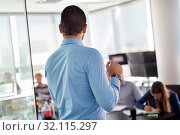 Business man making a presentation at office. Business executive delivering a presentation to his colleagues during meeting or in-house business training. Rear view. Shalow depth of field. Стоковое фото, фотограф Zoonar.com/Matej Kastelic / age Fotostock / Фотобанк Лори