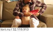 Купить «Unrecognizable parent dressing little baby in t shirt», видеоролик № 32119913, снято 23 августа 2019 г. (c) Ekaterina Demidova / Фотобанк Лори