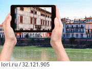 Travel concept - tourist photographs houses on waterfronts in Verona city in Italy in spring on tablet. Стоковое фото, фотограф Zoonar.com/Valery Voennyy / easy Fotostock / Фотобанк Лори