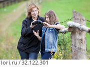 Mother gives binoculars young daughter and explains how to use it, woman and girl in farmland. Стоковое фото, фотограф Кекяляйнен Андрей / Фотобанк Лори