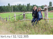 Mature mother and teenage daughter portrait on countryside, sitting together on wooden fence in pasture, female farmers, copy space. Стоковое фото, фотограф Кекяляйнен Андрей / Фотобанк Лори