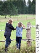 Купить «Adult mother and her young daughter enjoying nature in countryside, standing close against the fence, rear view», фото № 32122309, снято 11 августа 2019 г. (c) Кекяляйнен Андрей / Фотобанк Лори