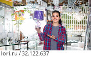 Купить «Girl 18-20 years old in lighter shop is choosing stylish and modern lamp», фото № 32122637, снято 16 февраля 2017 г. (c) Яков Филимонов / Фотобанк Лори
