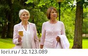 Купить «senior women or friends drinking coffee at park», видеоролик № 32123089, снято 25 августа 2019 г. (c) Syda Productions / Фотобанк Лори