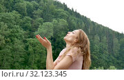 Young attractive blonde girl with red manicure and pink dress is standing under cold spring or autumn rain over mountain with green forest background. Стоковое видео, видеограф Ольга Балынская / Фотобанк Лори