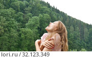 Купить «Young attractive blonde girl with red manicure and pink dress is standing under cold spring or autumn rain over mountain with green forest background», видеоролик № 32123349, снято 28 июля 2019 г. (c) Ольга Балынская / Фотобанк Лори
