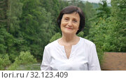 Close up portrait of an older woman with short dark hair and wrinkled face looking at the camera with smile on mountain hill with green forest on background. Стоковое видео, видеограф Ольга Балынская / Фотобанк Лори