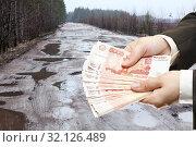 Купить «Руки держат российские рубли на фоне старой асфальтированной дороги, полной выбоин, коллаж», фото № 32126489, снято 13 апреля 2014 г. (c) Кекяляйнен Андрей / Фотобанк Лори