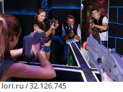 Купить «Excited people playing enthusiastically laser tag game», фото № 32126745, снято 27 августа 2018 г. (c) Яков Филимонов / Фотобанк Лори