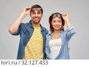 Купить «happy couple in sunglasses over grey background», фото № 32127433, снято 17 марта 2019 г. (c) Syda Productions / Фотобанк Лори