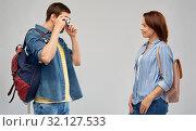 Купить «happy couple of tourists with backpacks and camera», фото № 32127533, снято 17 марта 2019 г. (c) Syda Productions / Фотобанк Лори