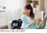 Купить «asian female blogger making video review of book», фото № 32127837, снято 13 апреля 2019 г. (c) Syda Productions / Фотобанк Лори