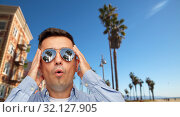 Купить «surprised man in sunglasses over venice beach», фото № 32127905, снято 22 июля 2015 г. (c) Syda Productions / Фотобанк Лори