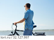 Купить «man with bicycle on summer beach looking far away», фото № 32127997, снято 23 июля 2017 г. (c) Syda Productions / Фотобанк Лори