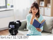 Купить «asian female blogger making video review of book», фото № 32128097, снято 13 апреля 2019 г. (c) Syda Productions / Фотобанк Лори