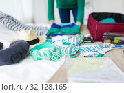 Купить «woman packing travel bag at home or hotel room», фото № 32128165, снято 18 января 2017 г. (c) Syda Productions / Фотобанк Лори