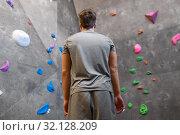 Купить «young man at indoor climbing wall in gym», фото № 32128209, снято 2 марта 2017 г. (c) Syda Productions / Фотобанк Лори