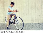 Купить «man with smartphone and fixed gear bike on street», фото № 32128545, снято 15 июня 2016 г. (c) Syda Productions / Фотобанк Лори