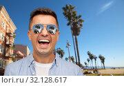 Купить «laughing man in sunglasses over venice beach», фото № 32128617, снято 22 июля 2015 г. (c) Syda Productions / Фотобанк Лори