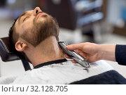 Купить «man and barber with trimmer cutting beard at salon», фото № 32128705, снято 6 апреля 2017 г. (c) Syda Productions / Фотобанк Лори