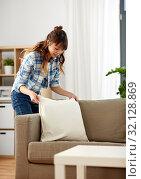 Купить «asian woman arranging sofa cushions at home», фото № 32128869, снято 13 апреля 2019 г. (c) Syda Productions / Фотобанк Лори