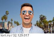 Купить «laughing man in sunglasses over venice beach», фото № 32129017, снято 22 июля 2015 г. (c) Syda Productions / Фотобанк Лори