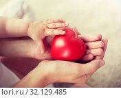 Купить «close up of baby and mother hands with red heart», фото № 32129485, снято 12 июля 2016 г. (c) Syda Productions / Фотобанк Лори