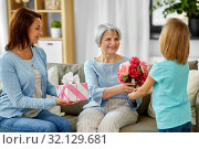 granddaughter giving flowers to grandmother. Стоковое фото, фотограф Syda Productions / Фотобанк Лори