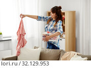 Купить «asian woman picking dirty laundry at home», фото № 32129953, снято 13 апреля 2019 г. (c) Syda Productions / Фотобанк Лори