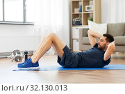 man making abdominal exercises at home. Стоковое фото, фотограф Syda Productions / Фотобанк Лори